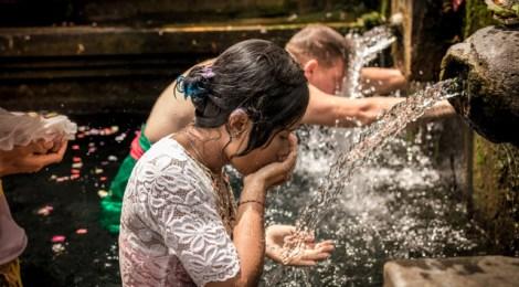 BALI, INDONESIA - DECEMBER 5, 2017: Holy spring water. People praying in the Tirta Empul temple. Bali.