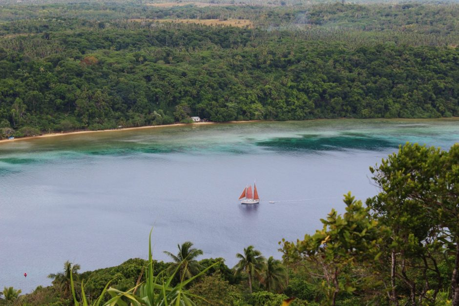 A sailboat moves through the harbour, Tonga