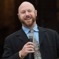 A bald white male with a beard is holding a wireless microphone and giving a hilarious speech.