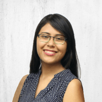 Cindy Ramirez, a young Latinx individual with a medium brown skin tone and dark brown hair past shoulder length. She is using full frame black and green glasses, and is wearing a sleeveless dark blue blouse patterned with white polka-dots. Cindy is smiling at the camera, standing in front of a light gray wall.