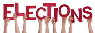 A photograph of several light skinned hands holding up red cut-out letters against a white background. The letters spell out the word elections in all caps.