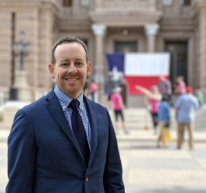 A white male in his mid-forties with brownish red hair and beard in a dark blue suit with blue tie. He is smiling proudly in front of the Texas State Capitol. In front of the Capitol in the background is a Texas flag that has been propped up for an event.