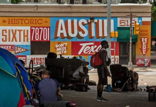 A group of people experiencing homelessness in front of an Austin mural