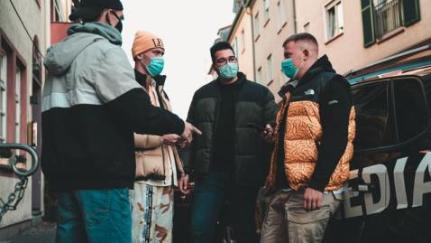 Group of people standing in a circle on a city sidewalk with masks on talking