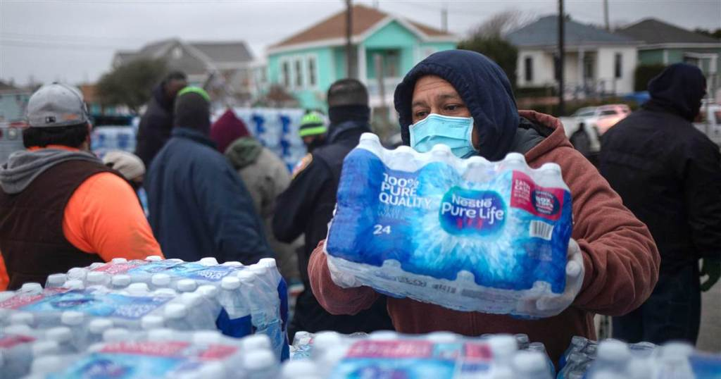 A person in winter gear and a mask picking up a case of water from a pallet of bottled water.