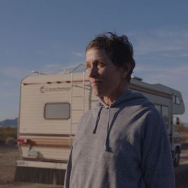 A scene from Nomadland with a person standing facing toward a setting sun with their RV in the background slightly blurred.