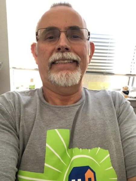 Advocate smiling at the camera taking a selfie in front of a window with his homelessness awareness day shirt