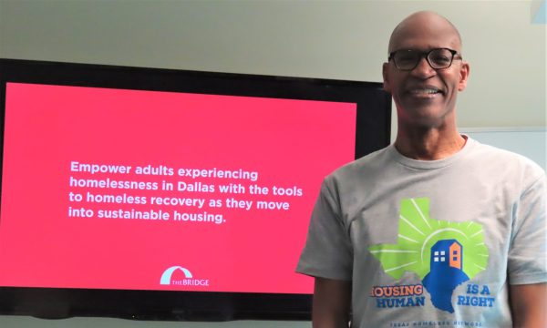 Dr. Woody smiling and standing in his homelessness awareness day shirt in front of a powerpoint about The Bridge Homeless Recovery Center.