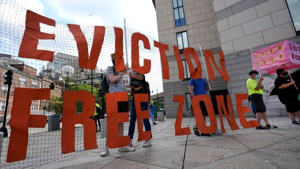 A protest sign that is see through on chicken wire that says Eviction Free Zone. It is held by multiple people standing behind it.