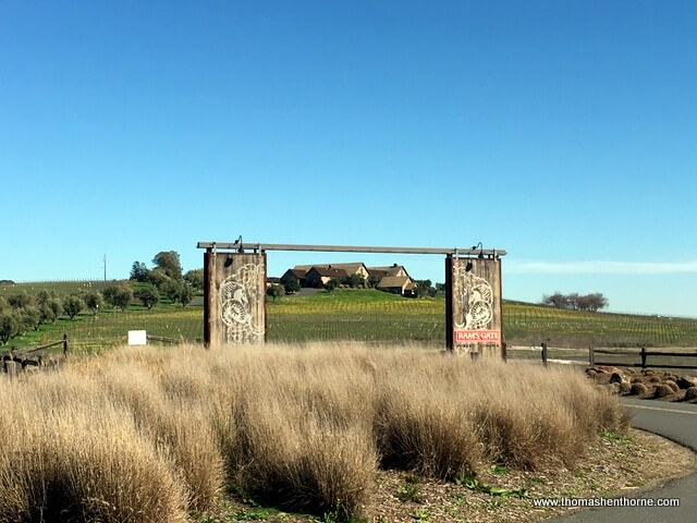 Entrance to Ram's Gate winery with large gate and building in background on a sunny day