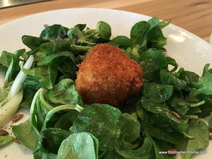 photo of fried camembert over greens