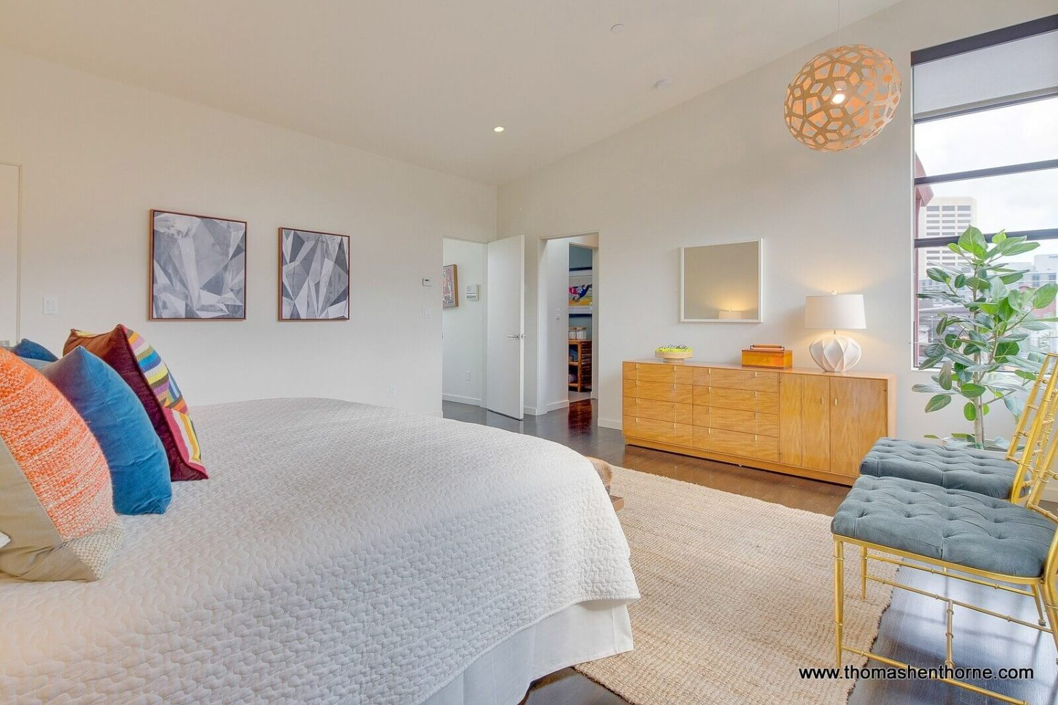 Photo of bedroom with two yellow chairs and modern hanging lamp