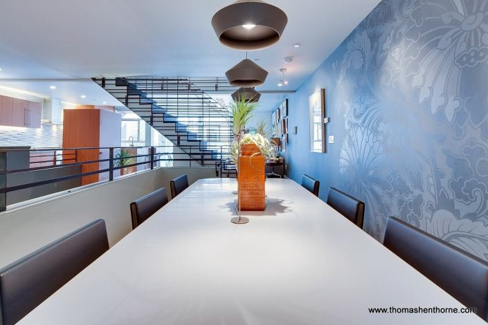 Dining area on mezzanine level with stairway in background