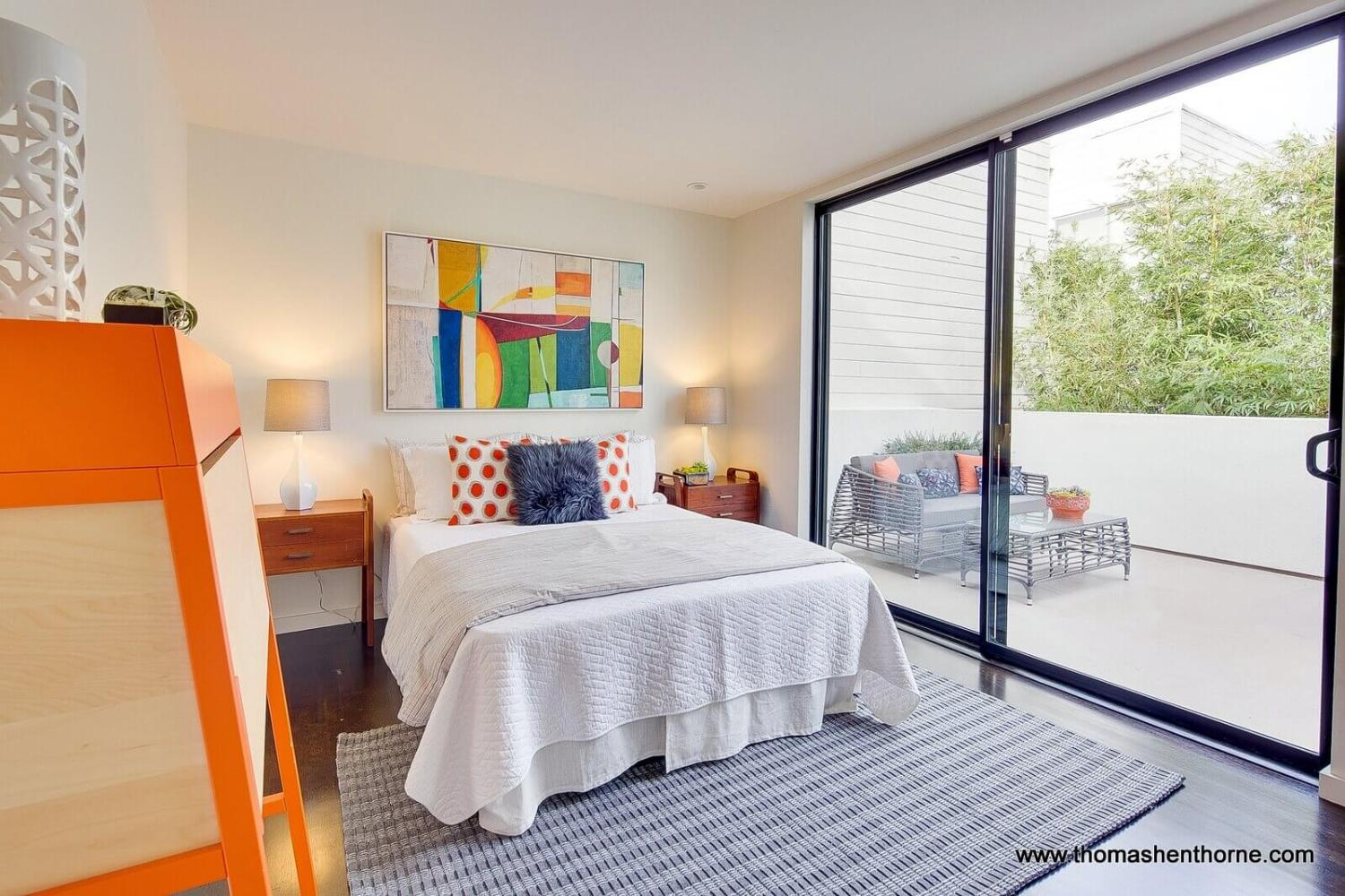 Guest bedroom at 124 Lily Place with glass sliding doors out to patio