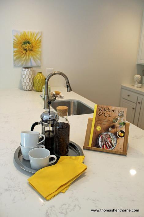 Kitchen counter with book and French press with coffee cups