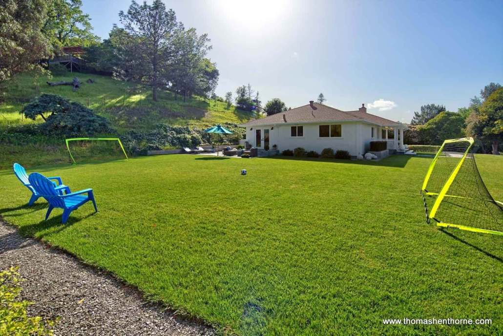 Expansive lawn with soccer goals and soccer ball
