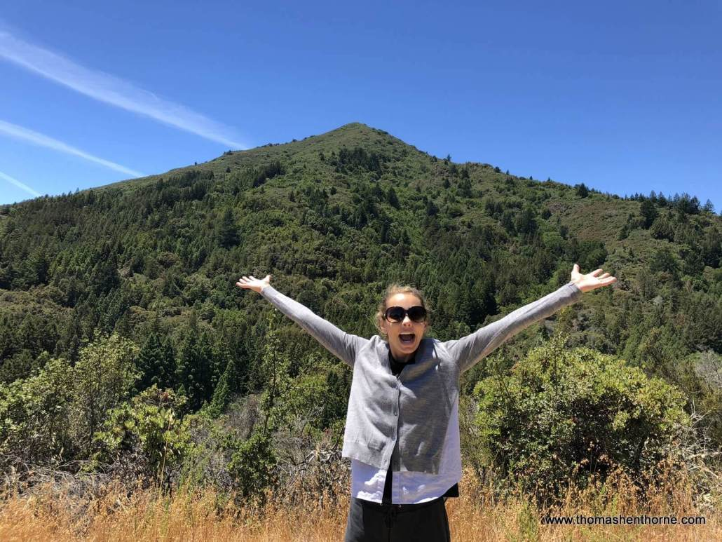 Woman with arms in air and Mount Tam in background