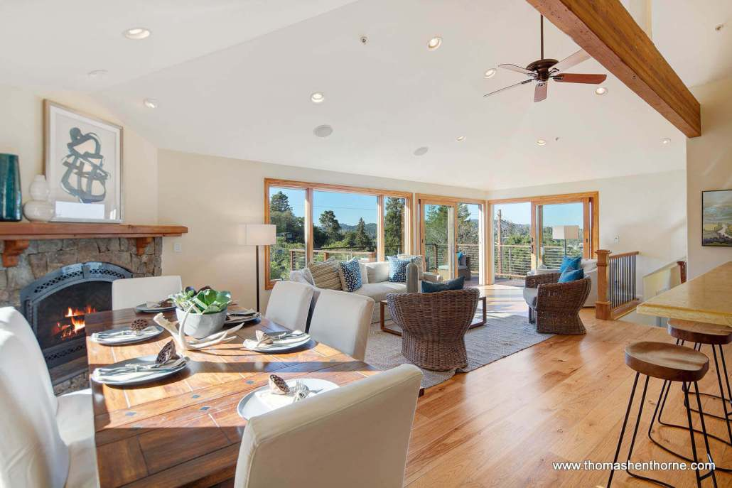 Dining and living area with fireplace and glass doors to outside deck