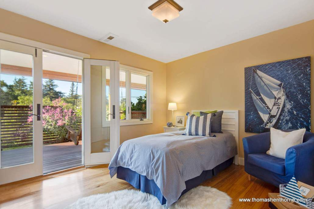 Bedroom with single bed and French doors to deck