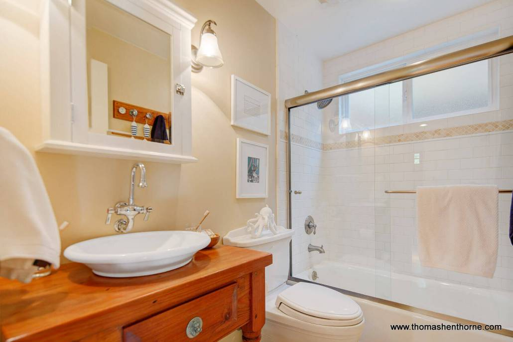 Bathroom with vessel sink and glass tub enclosure
