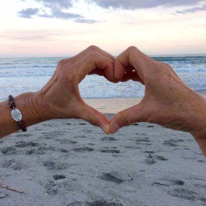 Sukha Yoga hands forming a heart on a beach