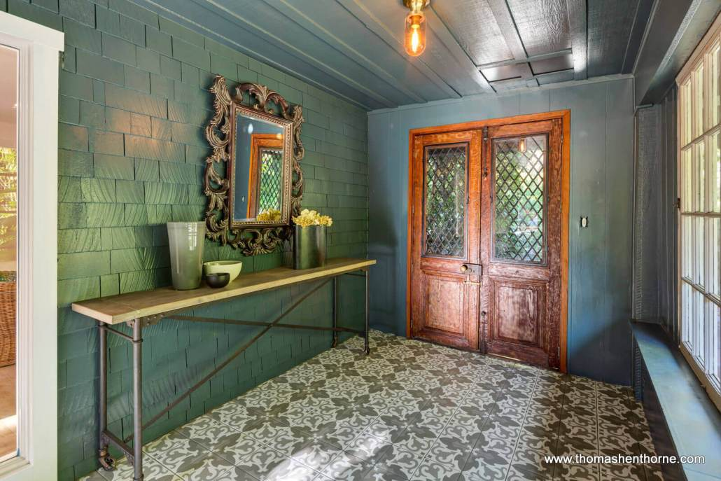 Enclosed porch with shingled walls and tile floors