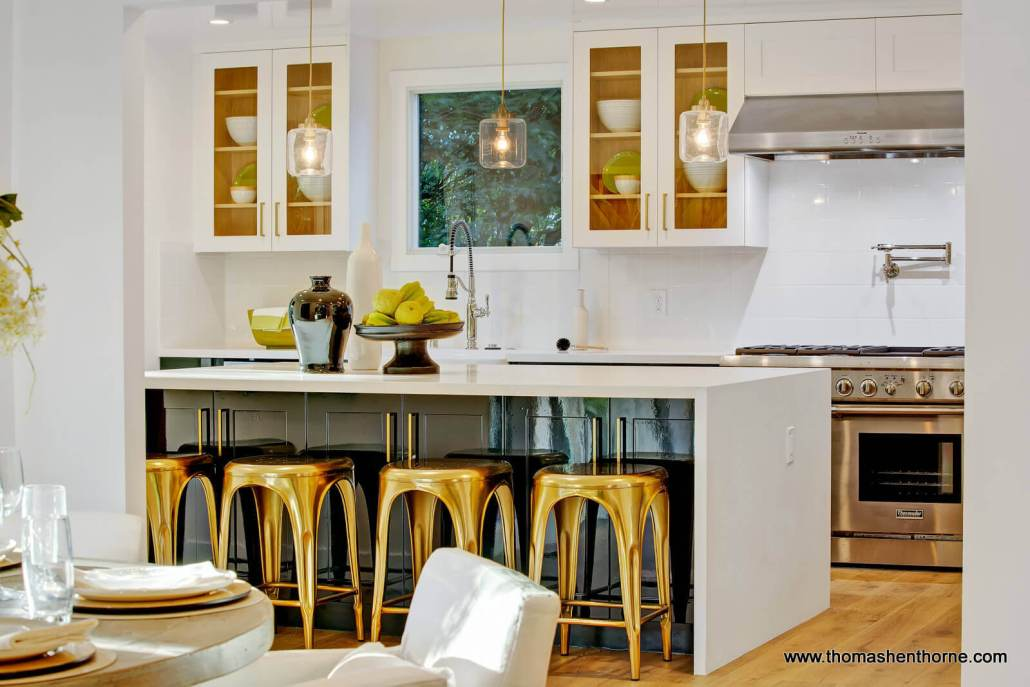 Modern kitchen with stainless appliances and gold stools
