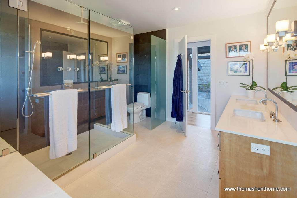 Large bathroom with glass-enclosed dual shower and double vanity
