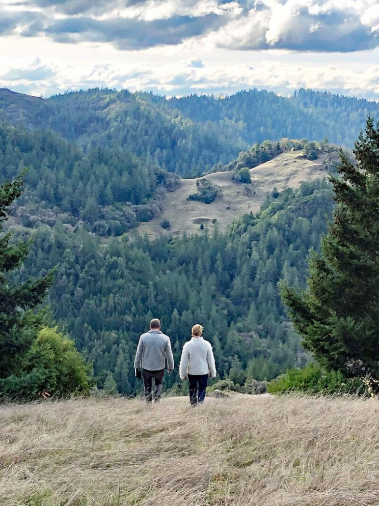 Two people walking amidst hills and nature on Longview Ranch