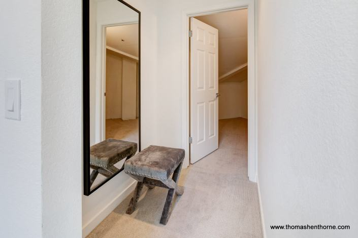 Hallway with mirror and door open to storage room