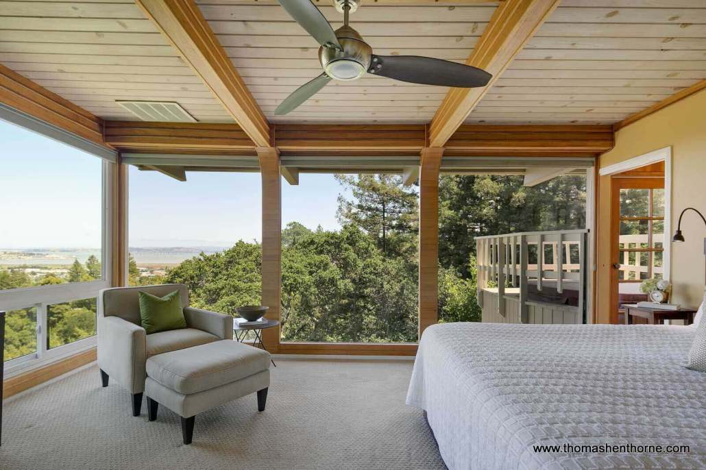 Master bedroom with walls of glass and views of bay