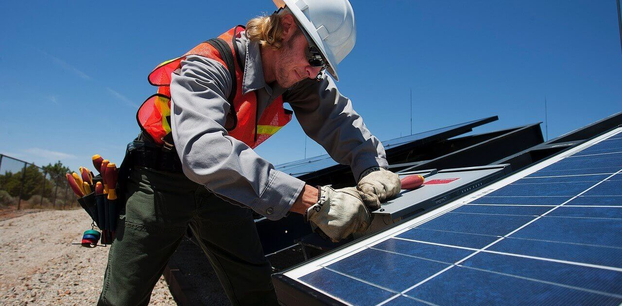 Man working on solar panels for solar lease article
