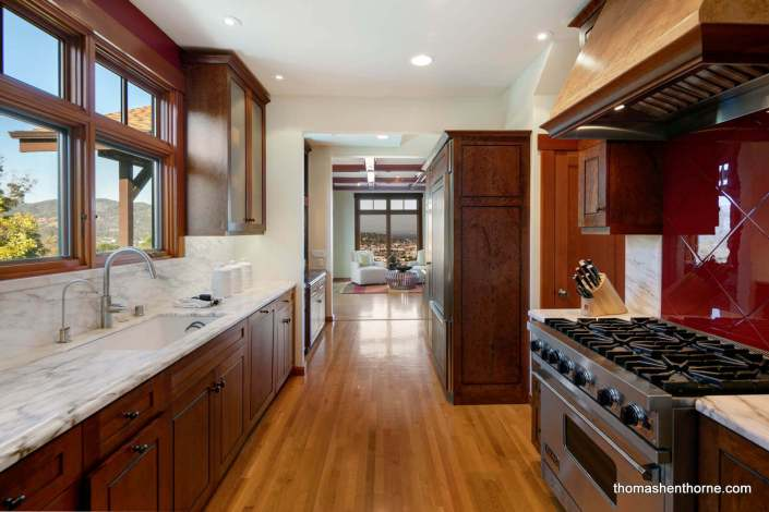 Galley kitchen with modern stainless appliances and marble countertops