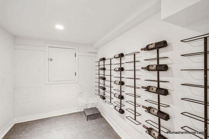 room with wine bottles on wall