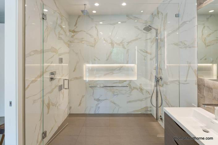 Walk-in marble clad shower with dual shower heads