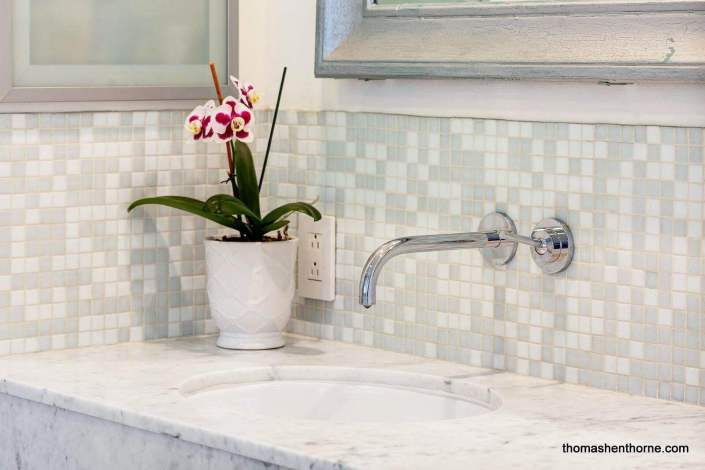Closeup of bathroom sink and orchid