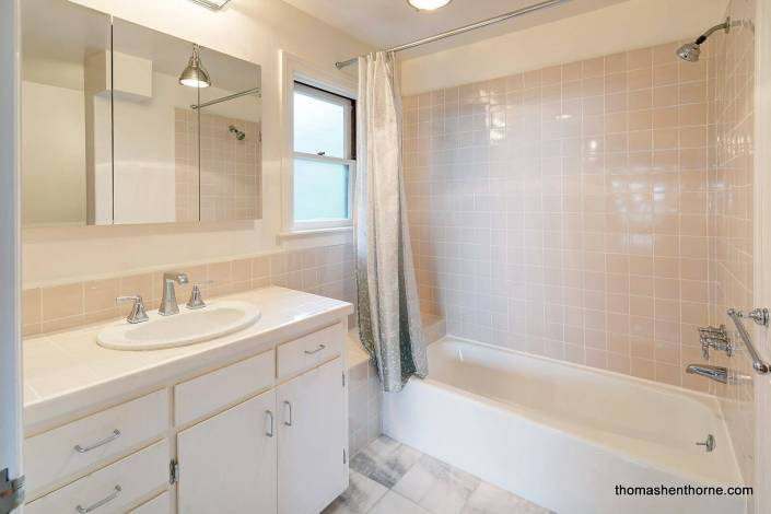 bathroom with shower tub combination and tile walls
