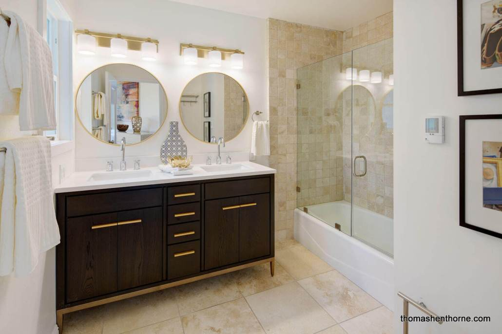 Master bathroom with dual sinks and glass enclosed tub shower