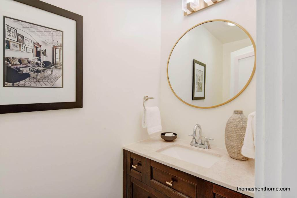 Powder room vanity with round mirror