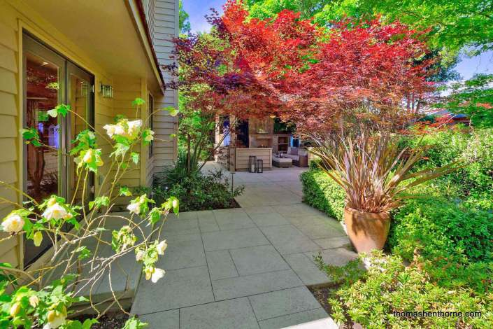 Lush back yard with stone paths and Japanese maple trees