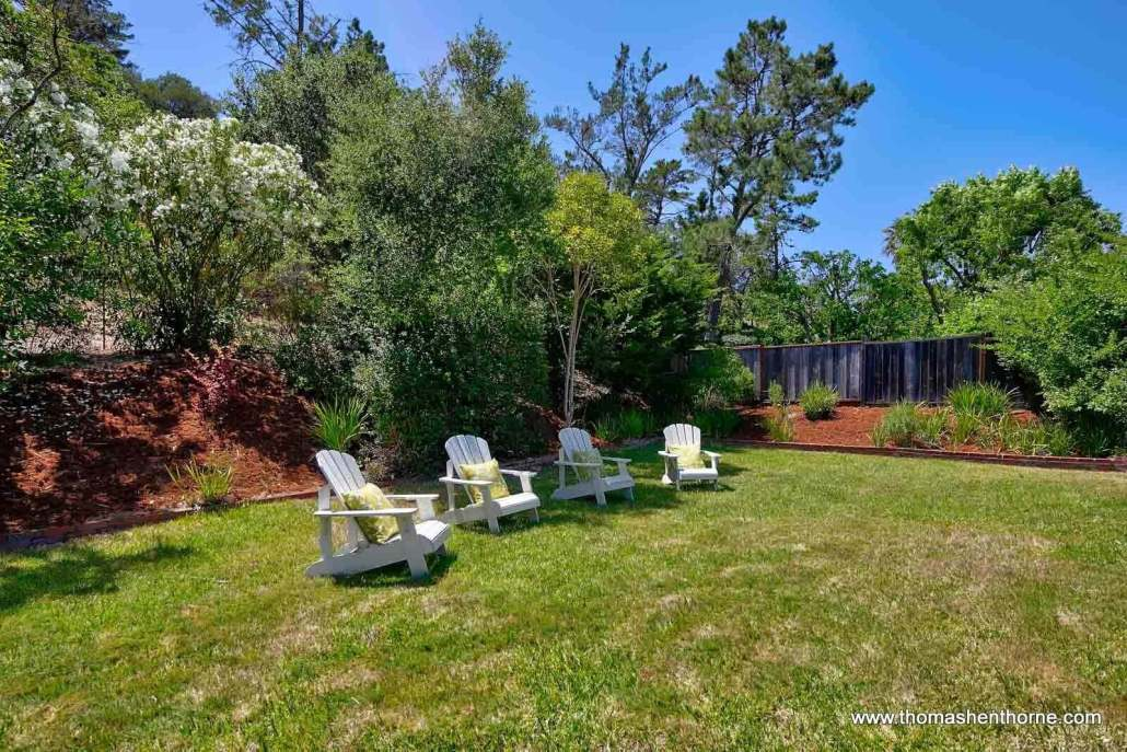 Four Adirondack chairs on green grass
