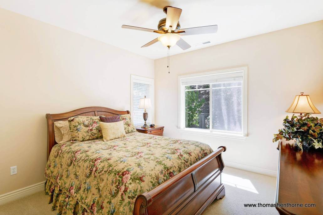Bedroom with sleigh bed and two windows and ceiling fan