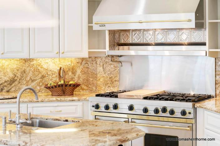 Viking stove with hood and granite countertops in kitchen