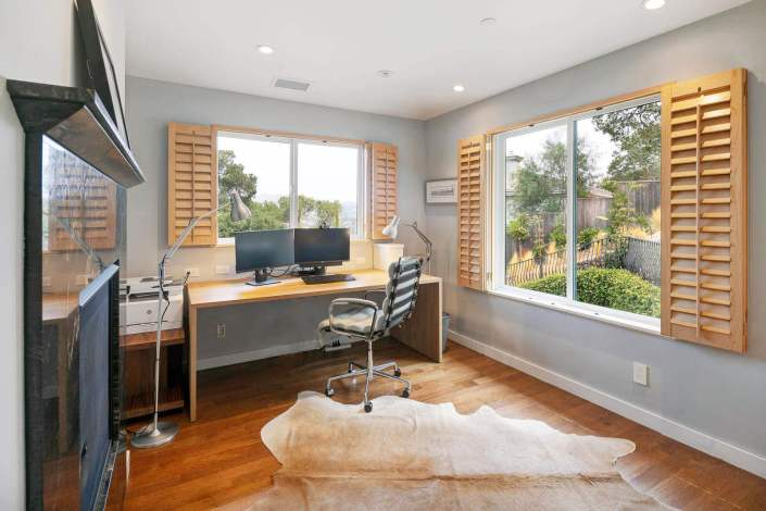 home office with wood floors and two windows