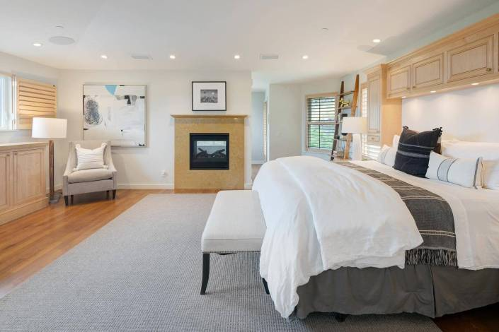 primary suite bedroom with king bed and custom cabinetry