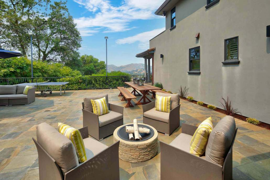 outdoor firepit with four chairs on stone terrace