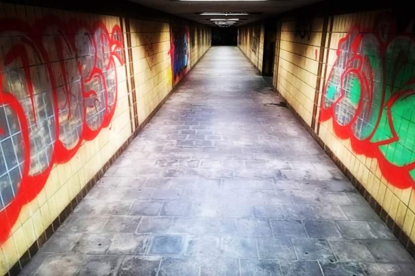 Ein Tunnel unter einem Bahnhof mit sehr viel bunten Graffities an den gekachelten Wänden rechts und links. © Tom Rübenach