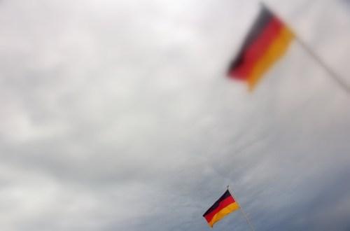 Zwei Deutschlandfahnen ragen in den bewölkten Himmel, eine ist verwaschen und damit unscharf.