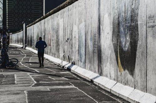 Ein Mann geht im Dunkeln an der Berliner Mauer entlang. Er ist nicht zu erkennen. Photo © Achim P. – pixabay