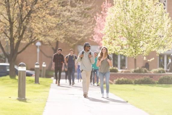 Estudantes que andam através do campus universitário